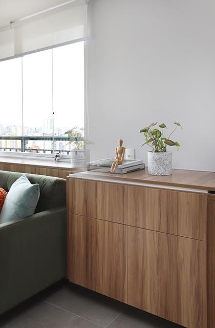 Móvel ao lado do sofá que esconde a pia sobre o tampo, um vaso com uma planta pequena, e um manequim para desenho