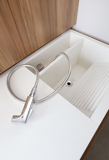 Pia branca com torneira flexível que pode ser escondida por um tampo de madeira