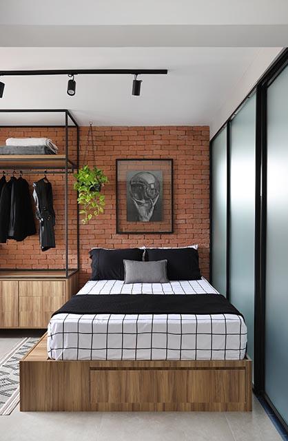 Cama com lençol branco com linhas pretas, sobre uma base de madeira, no quarto com parede de tijolos laranja