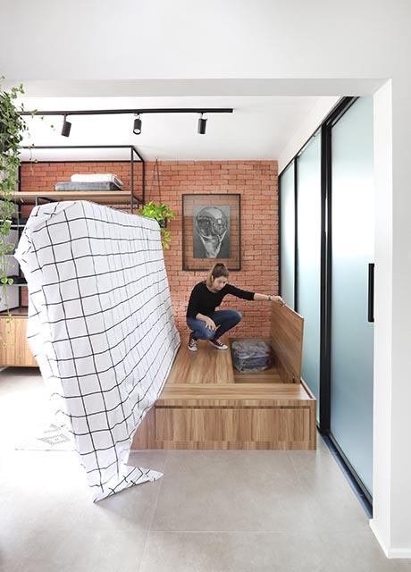 Colchão sendo levantado mostrando armário para armazenamento abaixo dele