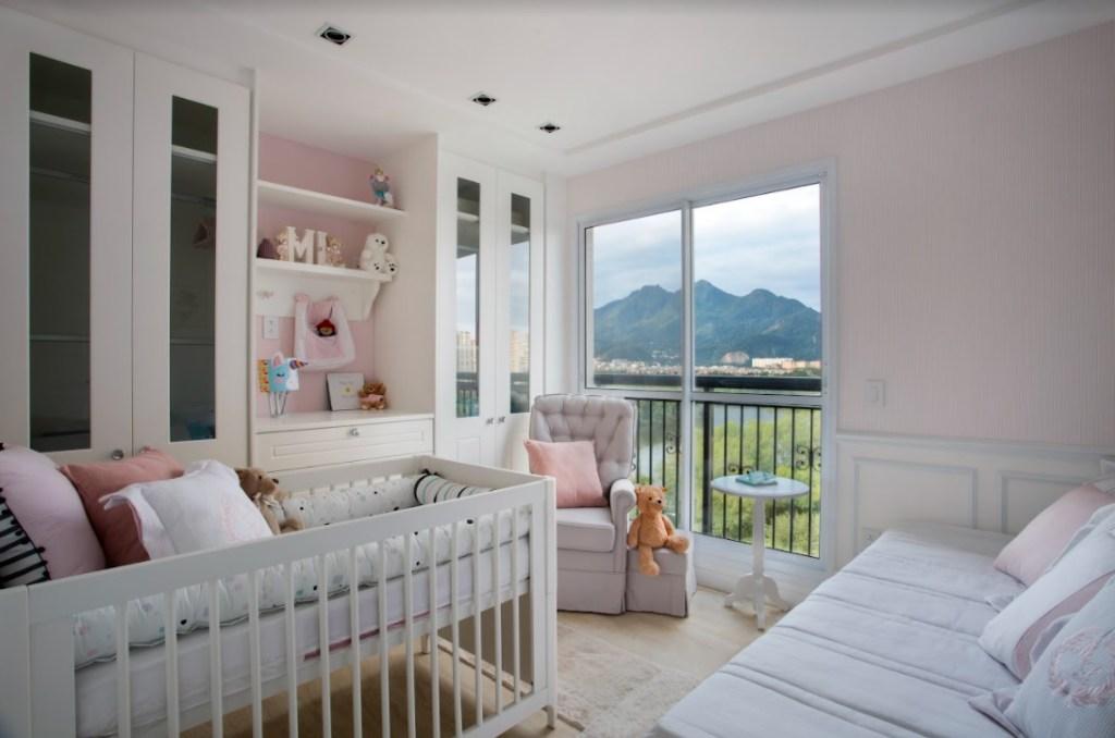 Quarto de bebê com berço, cama, poltrona e armários brancos. Parede rosa, ursinhos na estante