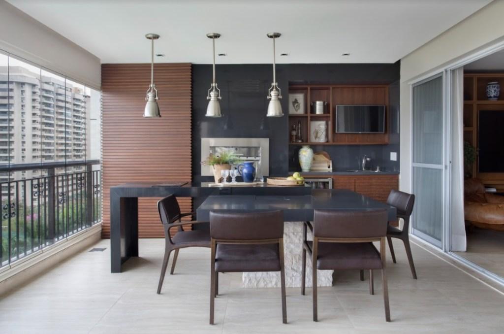 Varanda com mesa preta e cadeiras em madeira com encostos pretos. Parede de madeira ripada com detalhes pretos