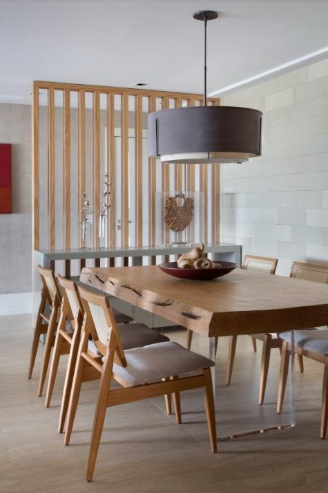Jantar com mesa de madeira e cadeiras de madeira. Luminária circular.
