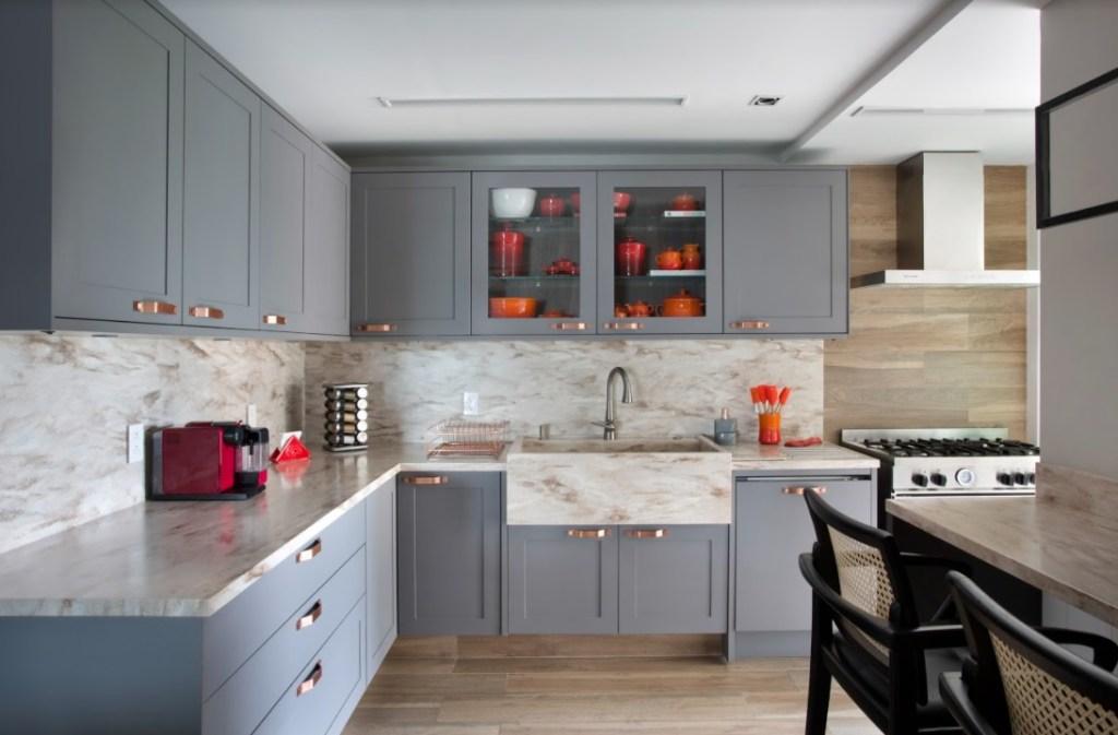 Cozinha com armários cinzas e bancada em mármore. Panelas laranjas em armário com porta de vidro