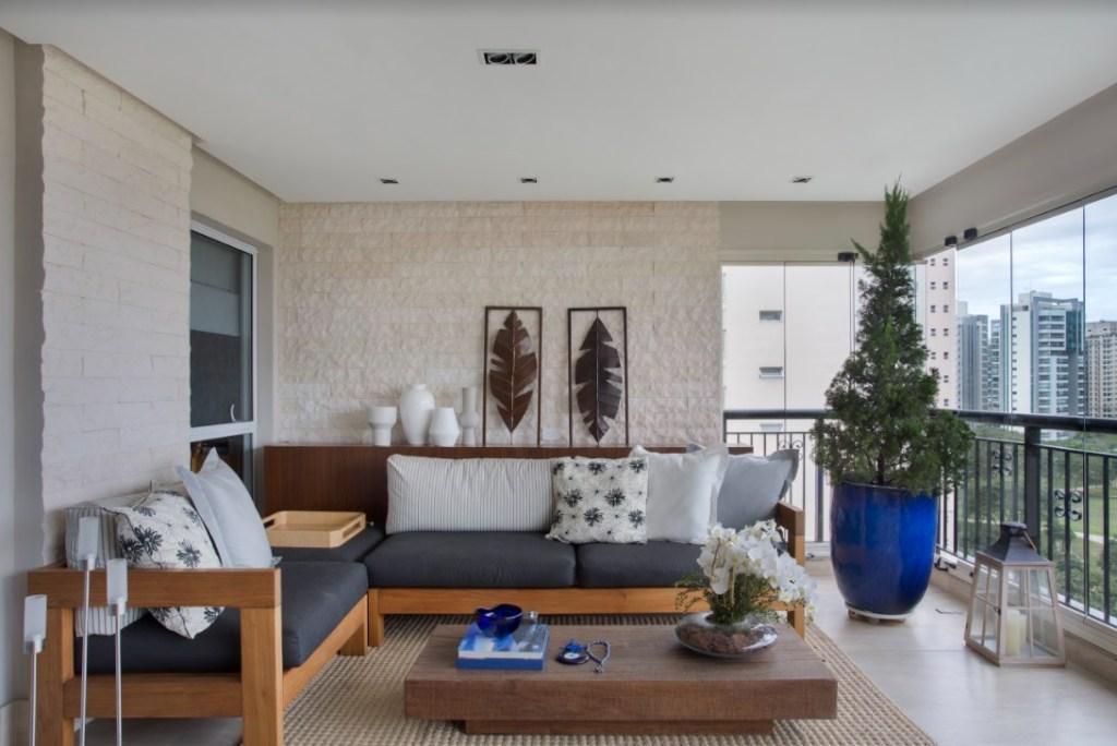Varanda com parede de tijolinhos. Sofá com almofadas brancas e azuis. Mesa de centro de madeira. Arvore pequena em vaso azul