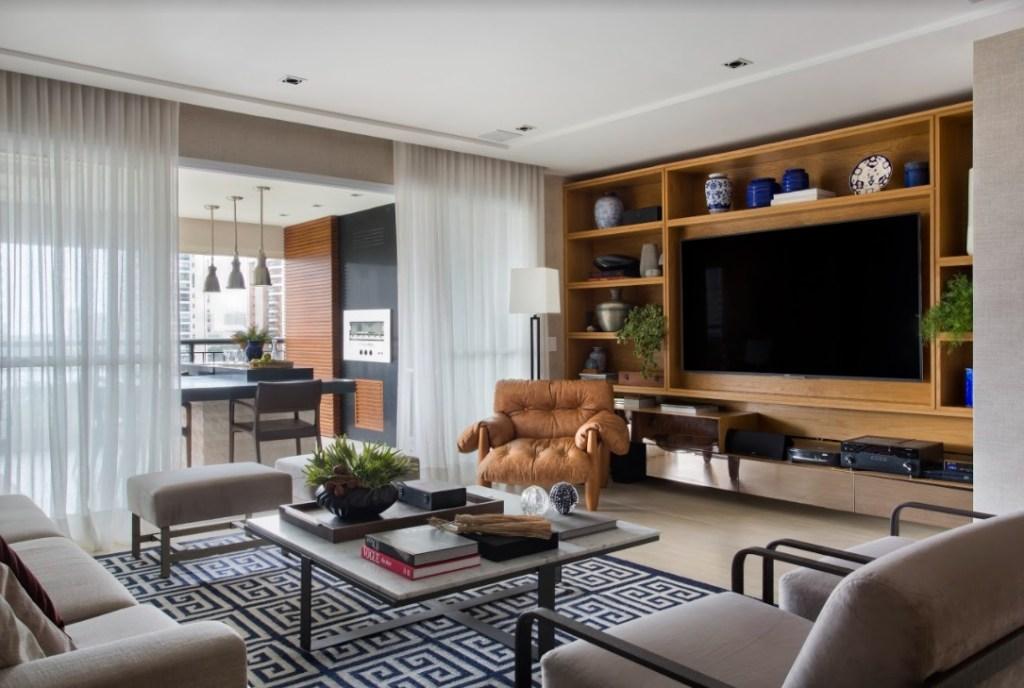 Living com tapete preto e branco. Sofás claros. Móvel de madeira com tv. Poltrona mole de Sergio Rodrigues