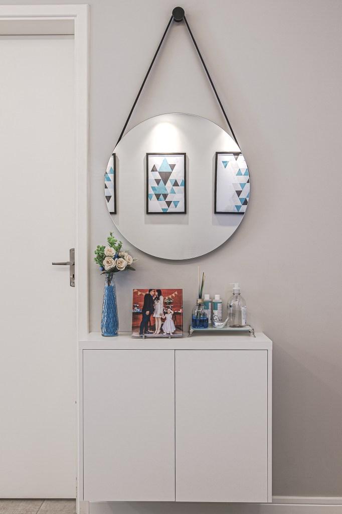 Pequeno aparador com aromatizador, porta-retrato e vasinho de flor. Espelho circular pendurado acima. Porta branca à esquerda