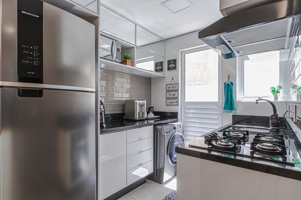 Cozinha com geladeira prateada. Balcão com cooktop preto. Armários em cima espelhados