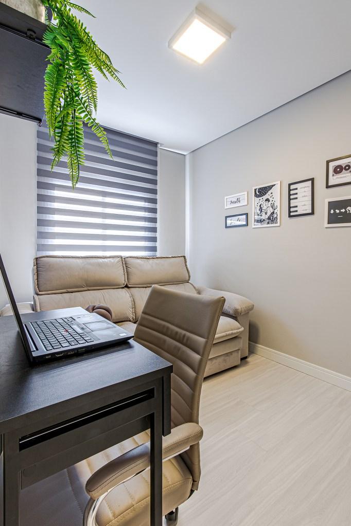 Quarto com sofá para dois lugares e pequenos quadros na parede. Mesa com computador e cadeira de escritório. Acima, samambaia.
