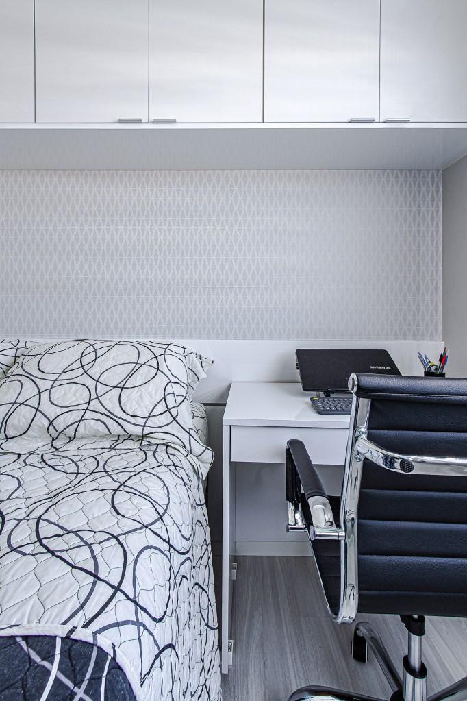 Cama de casal com armários acima. Ao lado uma pequena mesa branca com computador e outra cadeira de escritório.