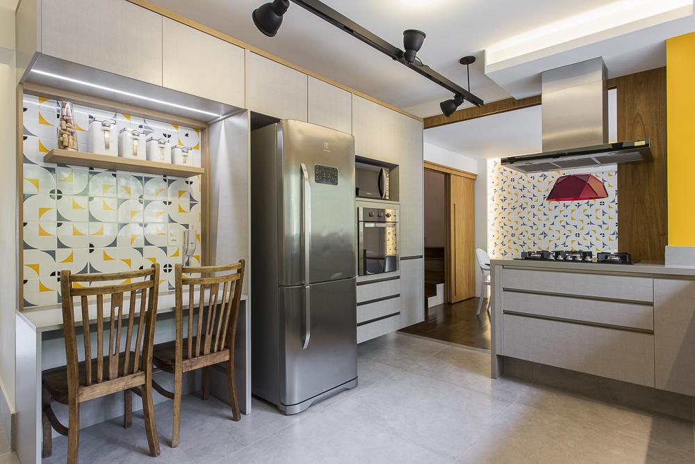 Cozinha com armários brancos e detalhes prateados. Pequena mesa de dois lugares e cadeiras de madeira. Parede amarela à direita. Pequena parede de azulejos à esquerda