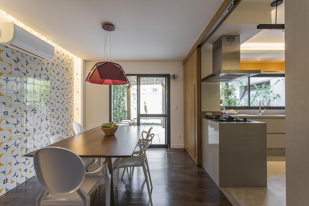 Sala de jantar integrada à cozinha. Parede de azulejos brancos, amarelos e azuis à esquerda. Bancada da cozinha à direita. Sacada ao fundo