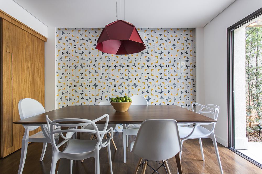 Mesa de jantar em madeira com cadeiras brancas; Parede com azulejos brancos com detalhes azuis e amarelos. Luminária geométrica vermelha escura.