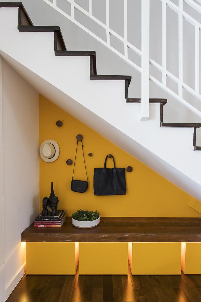 Canto embaixo da escada com balcão pequeno em madeira. Parede amarela. Bolsas penduradas.