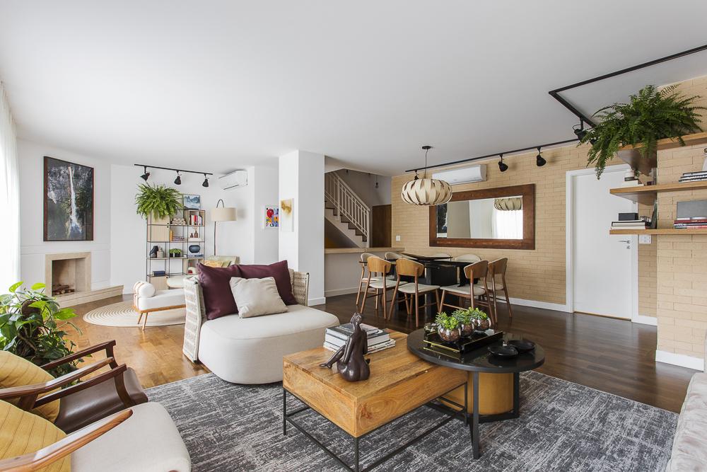 Living integrado com piso de taco. Sofá branco. Tapete cinza. Mesa de centro em madeira