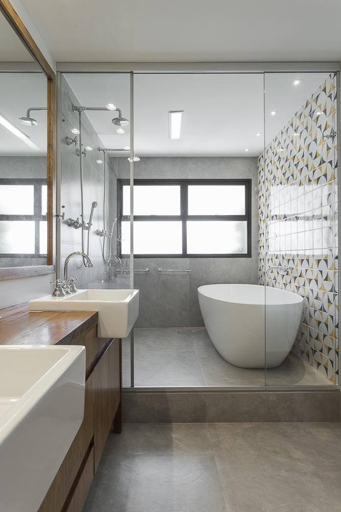 """Banheiro com banheira branca """"solta"""". Piso cinza tom concreto queimado. Parede de azulejos à direita."""