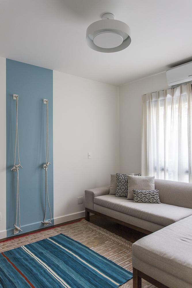 Sala de yoga com parede com detalhe azul e cordas penduradas. Sofá neutro à direita.