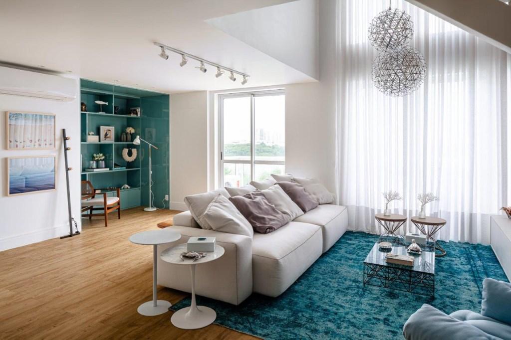 Living com sofá branco, tapete azul turquesa. Luminária esférica. Janelas grande ao fundo. Piso em madeira clara. Estante em azul ao fundo