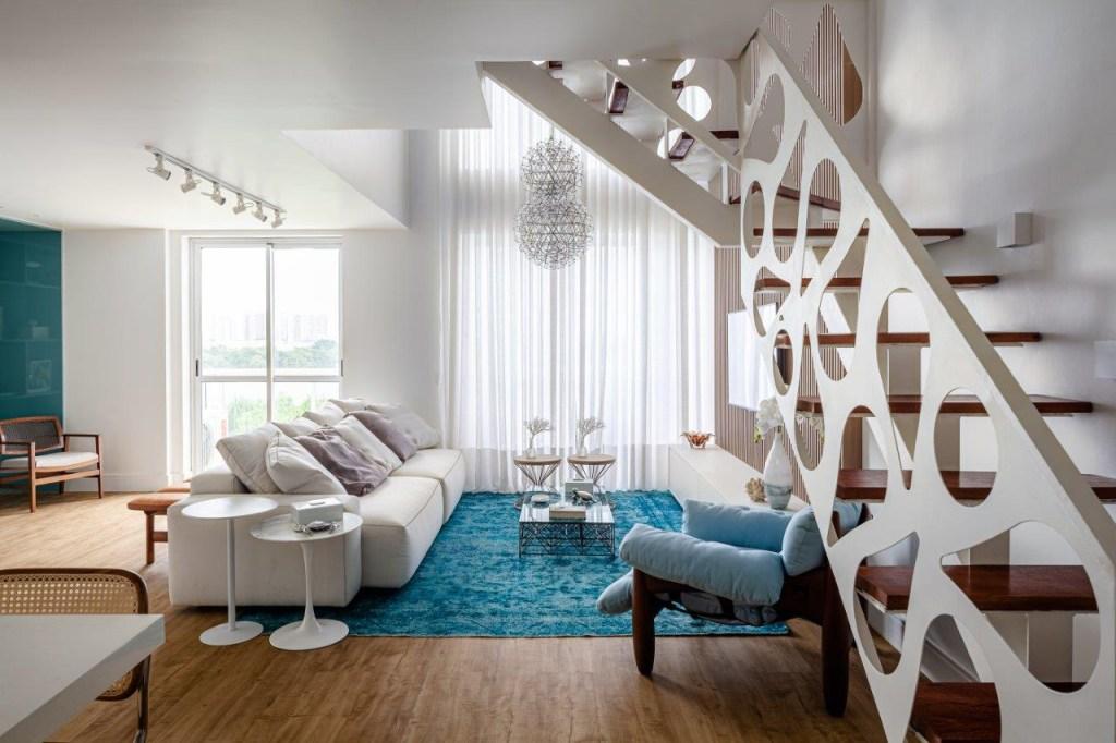 Living com tapete azul e sofá branco. Poltrona mole de Sergio Rodrigues em azul. Na lateral direita, escada com guarda-corpo branco metálico com furos em formato de gota