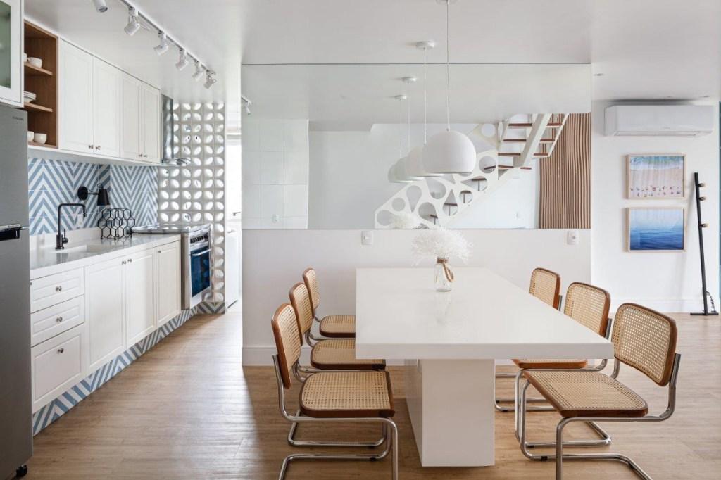 Sala de jantar com mesa branca de seis lugares. Cozinha integrada ao fundo na esquerda com parede de azulejos azuis e brancos no padrão listrado. Cobogós brancos ao fundo da cozinha. Escada ao fundo no centro refletido no espelho.
