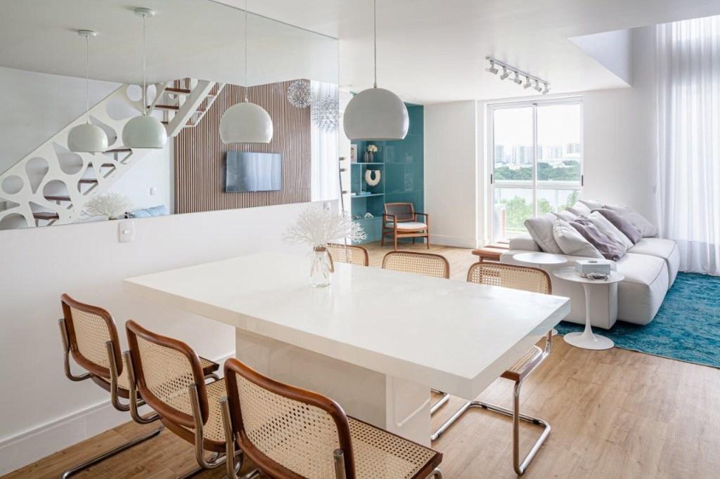 Living integrado com sala de jantar. Mesa branca com cadeiras em madeira com encostos em treliça; janelas ao fundo. Escada do lado direito