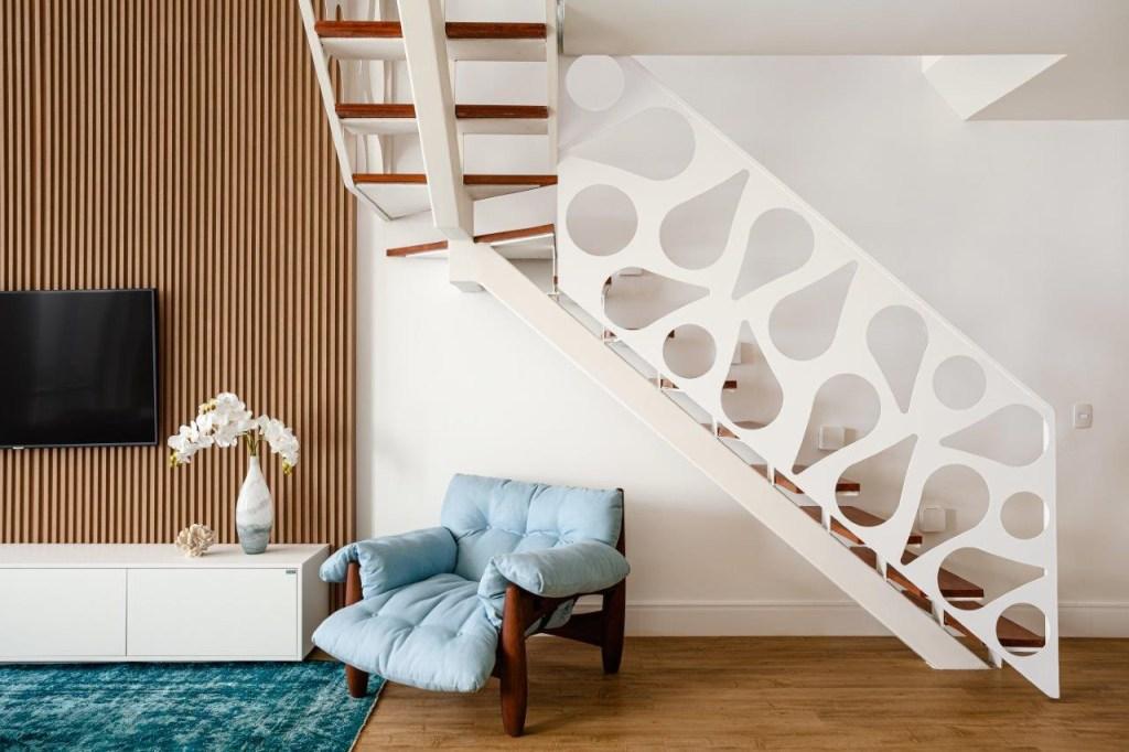 Escada branca com guarda-corpo metálico e furos em formato de gota. Poltrona Mole de Sergio Rodrigues.