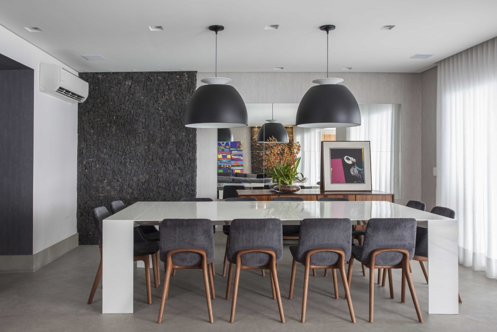 Sala de jantar com mesa de vidro branca e cadeiras com pernas de madeira e estofado cinza, com dois pendentes