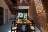 Sala de jantar com iluminação natural por conta da abertura entre os dois blocos da casa revestida em tijolo