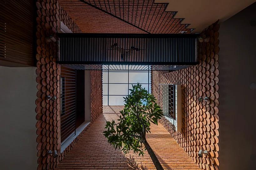 Casa revestida com tijolos e telhas tem um pátio e apassarela entre os dois blocos as construções de dois andares