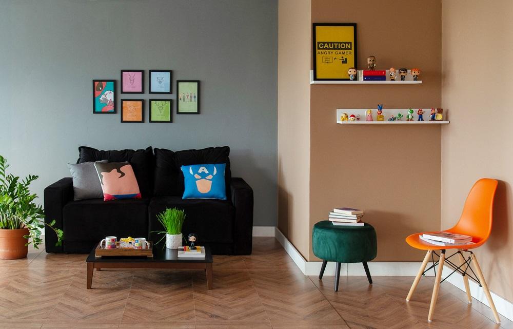 Sala com piso em madeira e sofá preto com almofadas de super heroi. Quadros na parede. Prateleiras com bonecos