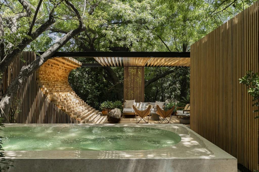 Patio com paredes em madeira ripada. Piscina de pedra clara. Árvores ao fundo.