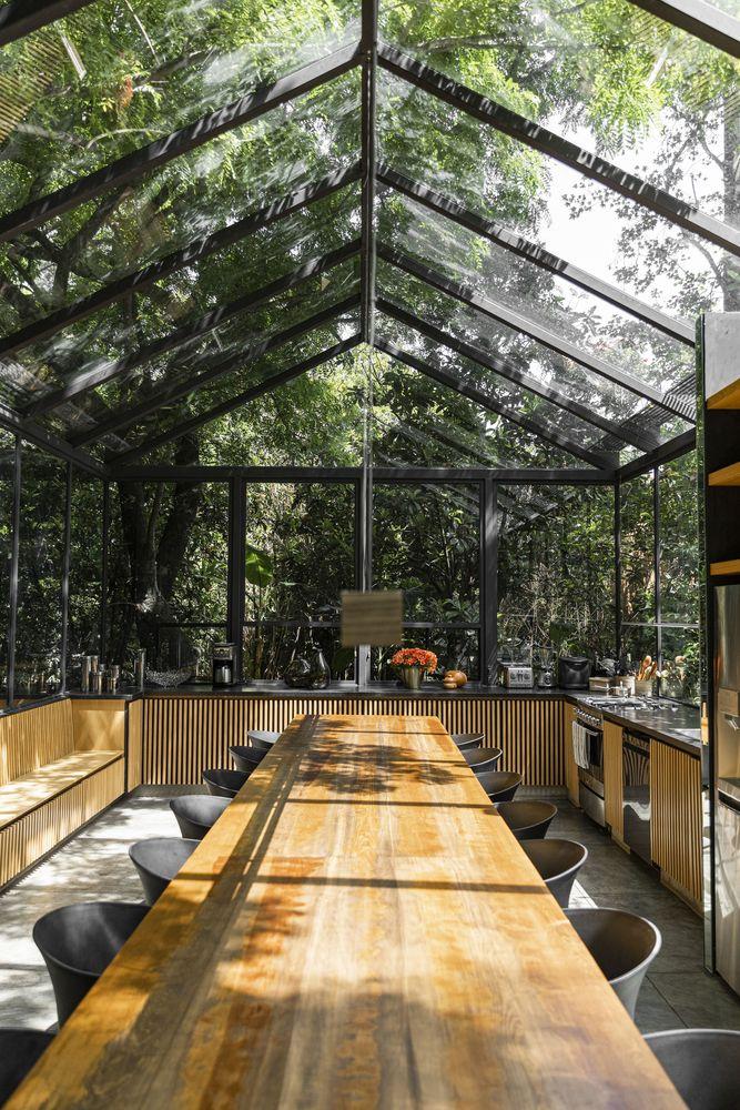 Cabana em vidro com mesa de madeira longa e várias cadeiras pretas. Bancada de cozinha em madeira ripada e pedra preta.