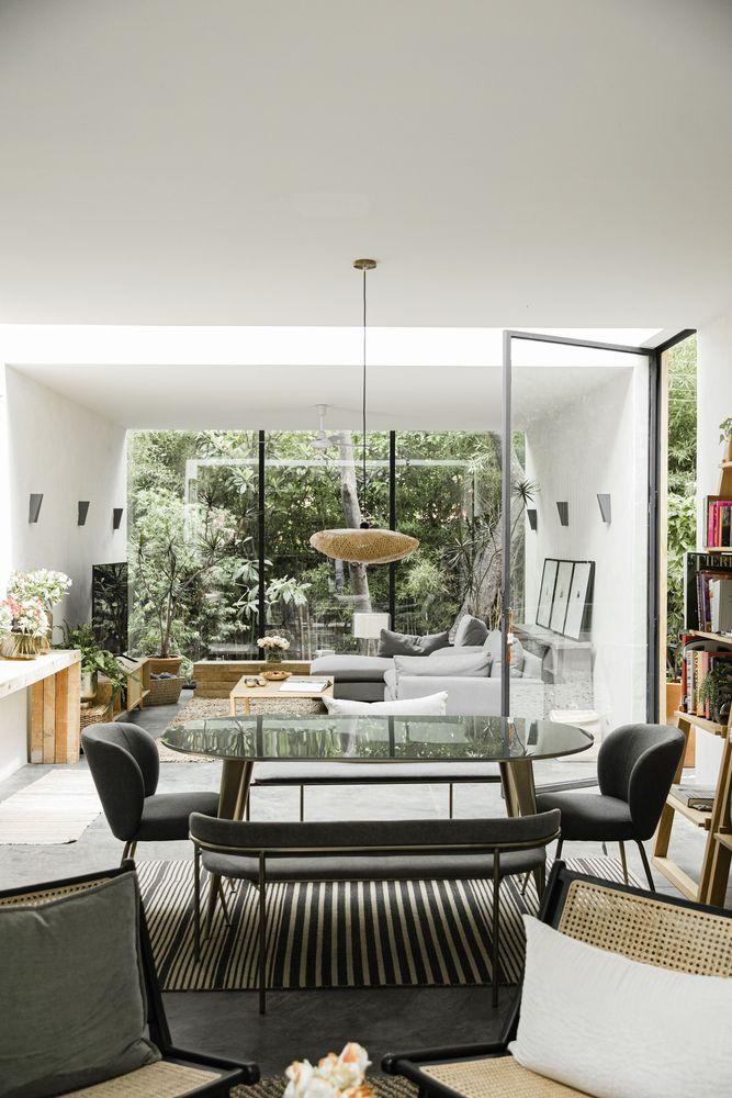 Living com grande janela como parede. Mesa de jantar à frente com três cadeiras pretas. Estante de livros do lado esquerdo. Sofá cinza ao fundo