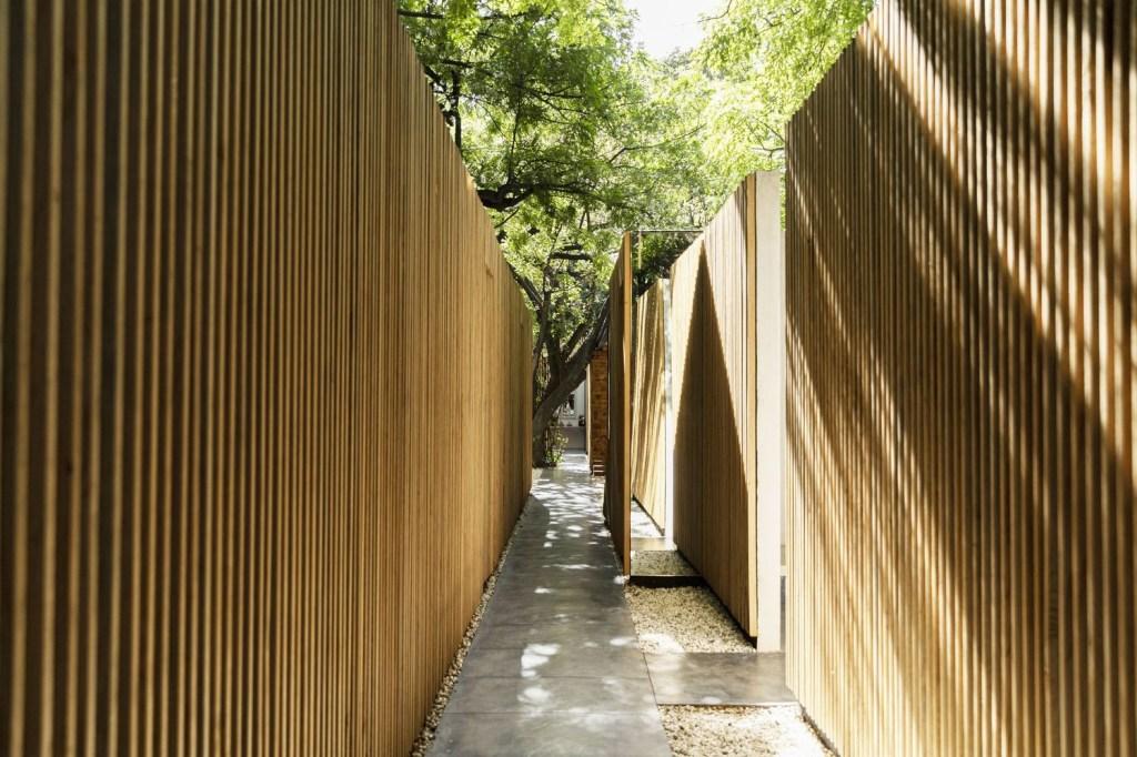 Espaço estreito externo entre duas paredes de madeira ripada. Ao fundo, um tronco de árvore cruza o caminho