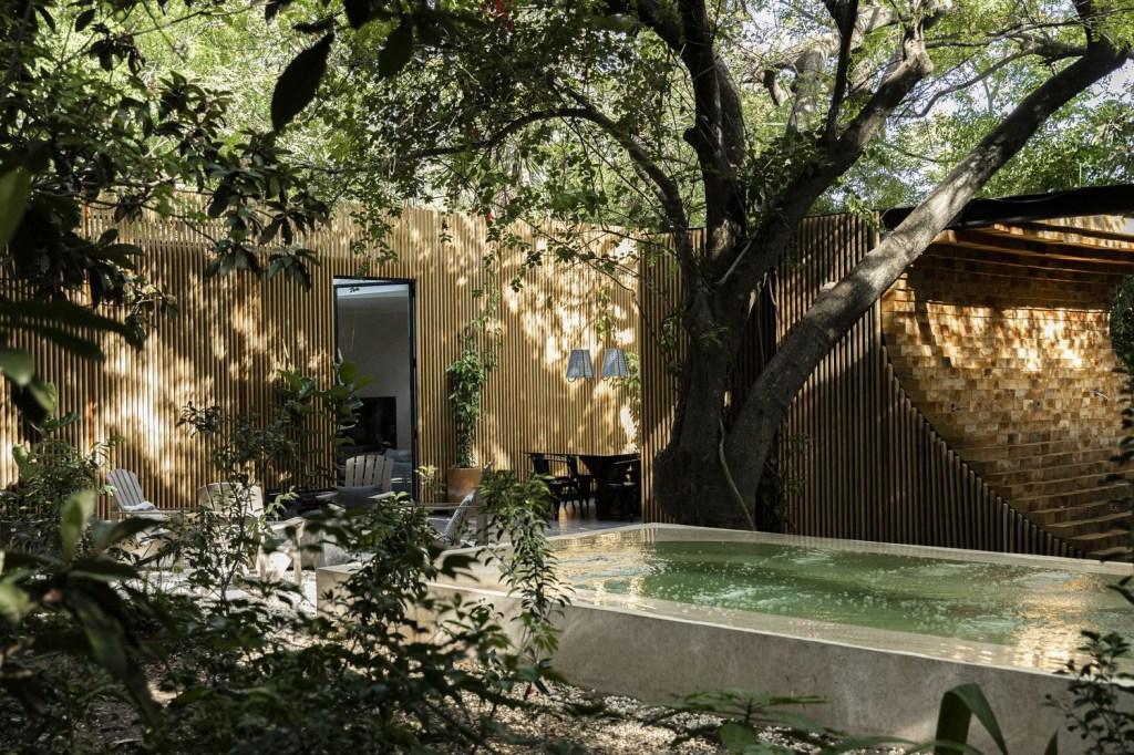 Patio com paredes em madeira ripada. Piscina de pedra clara. Área com cadeiras de madeira brancas