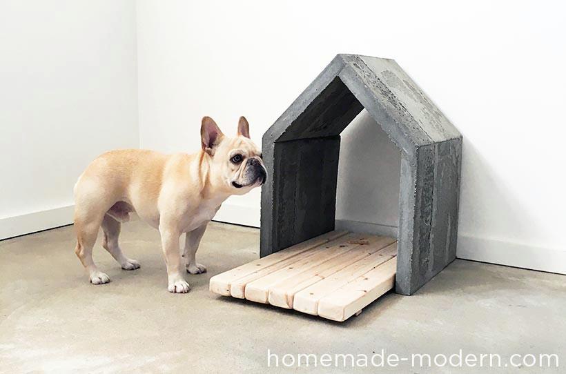 Casinha de cachorro feita de concreto com um deck de madeira para o cão deitar