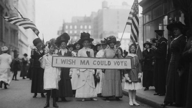 """Sufragistas nos Estados Unidos em 1913. No cartaz, """"queria que mamãe pudesse votar"""""""