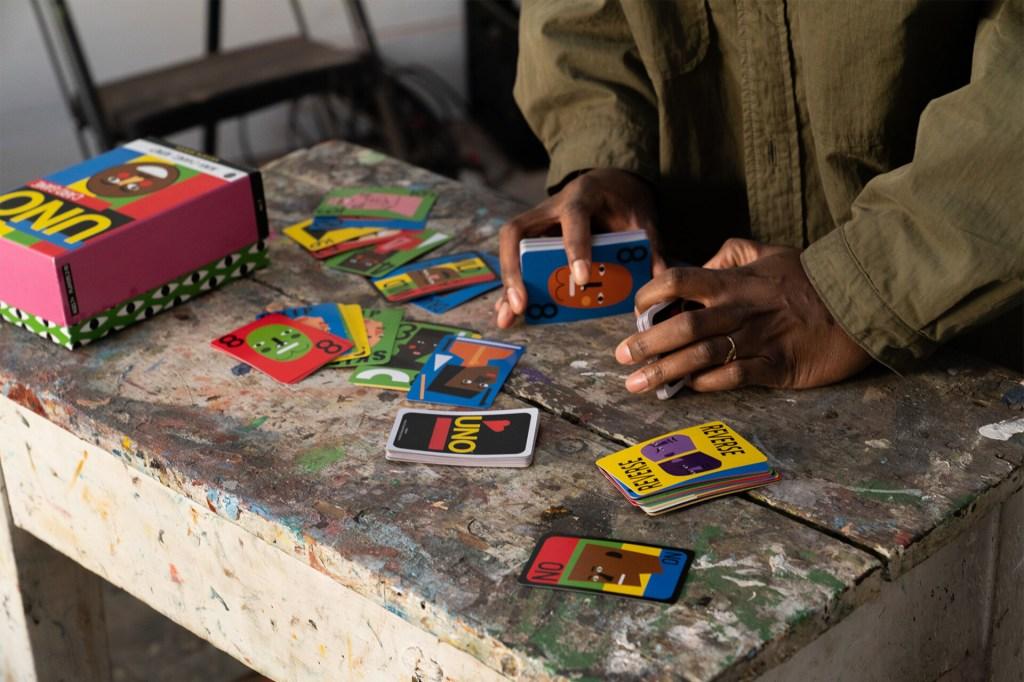 Cartas de UNO espalhadas em uma mesa de cimento queimado, com um par de mãos mexendo nelas