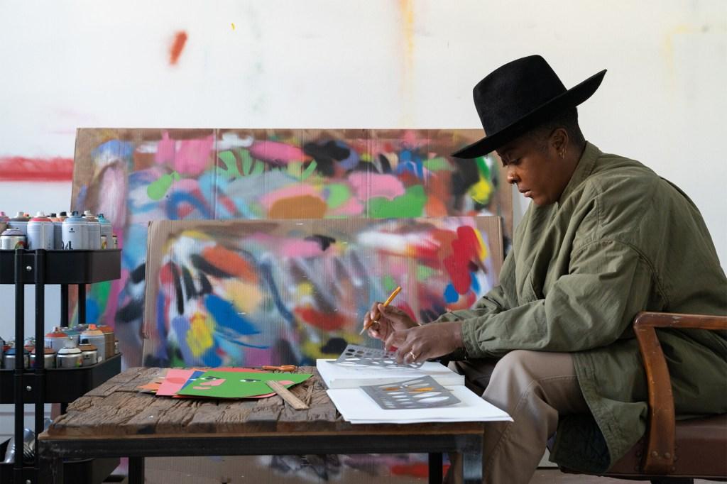 Artista Nina Chanel Abney sentada à mesa desenhando