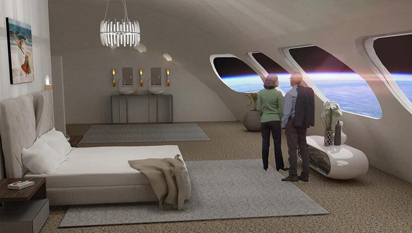 Quarto na cor bege com um cama e duas pessoas olhando pela janelas que dá vista para o espaço e para a Terra