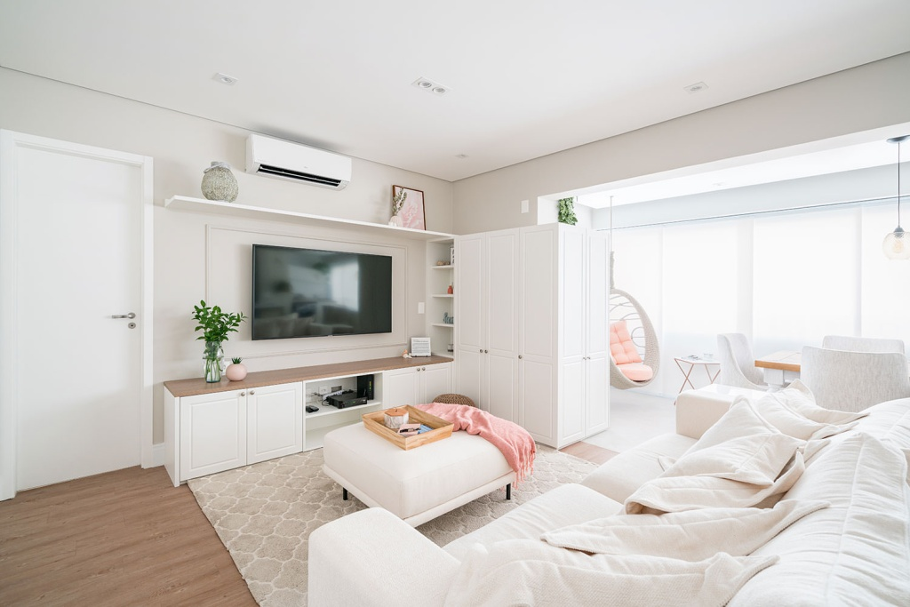 Estar com sofá branco e pufe branco com manta rosa. Televisão pendurada na parede. Ao fundo, balanço com almofada rosa
