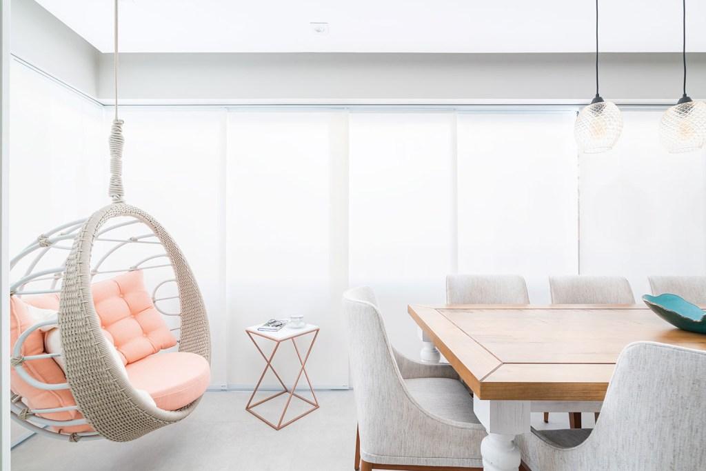 Balanço de corda com almofadas rosa. À direita, mesa de madeira com cadeiras de estofado cinza