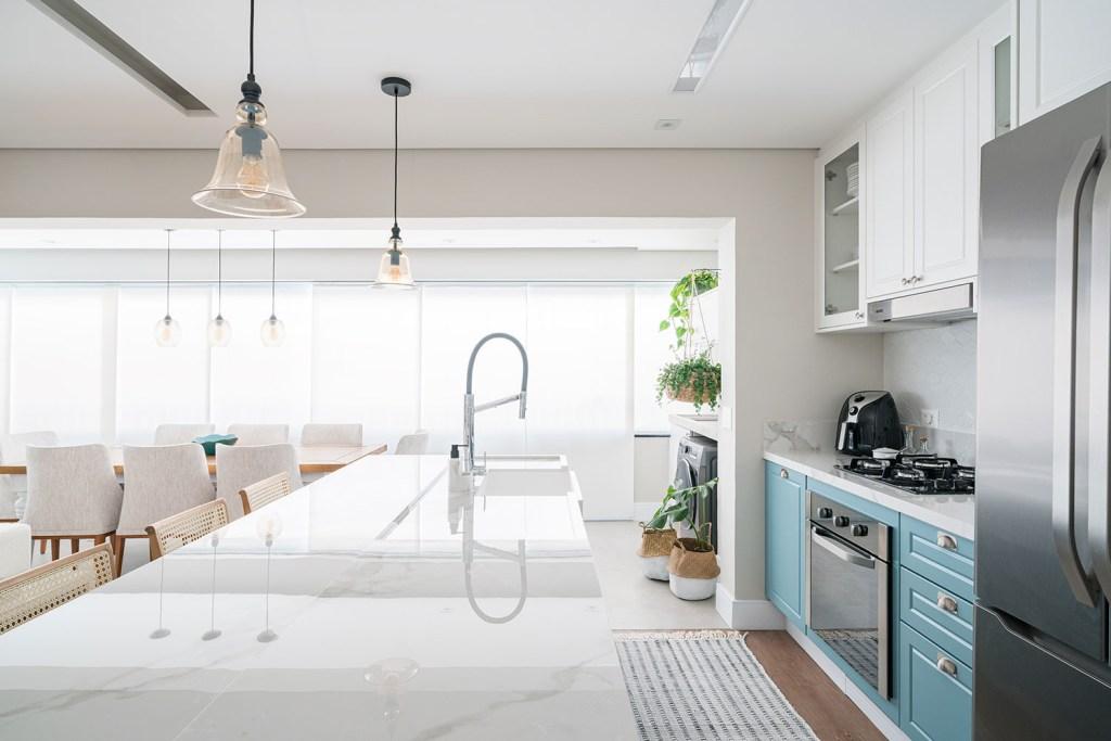 Ilha com bancada de pia em mármore branco. À direita, geladeira e bancada com armários azuis. Ao fundo, mesa de jantar em madeira com cadeiras cinzas