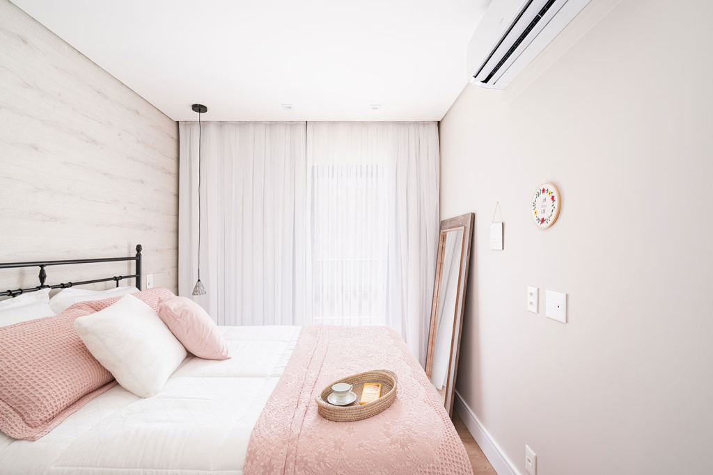 Quarto com cama de casal, Manta rosa e almofadas brancas e rosa