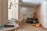 Sala de leitura com piso em madeira e uma das paredes em madeira. Parede branca com pinceladas em rosa salmão. Sofá cinza ao fundo.