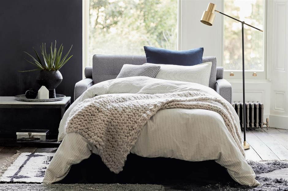 Sofá-cama montado com cobertas e travesseiros