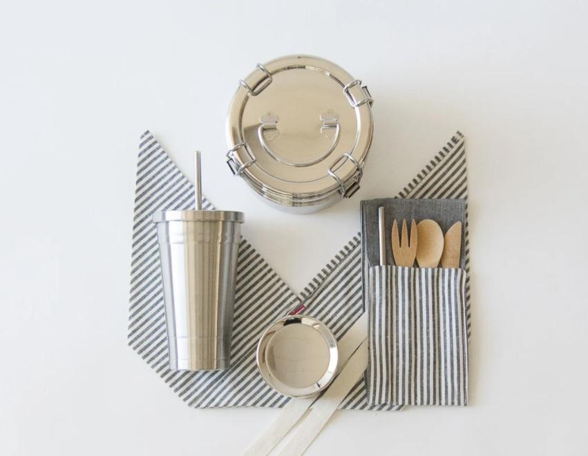 guardanapo de pano listrado dobrado em mesa branca. Copo de alumínio com canudo. Talheres de madeira. Marmita em alumínio