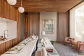 Jantar e estar em madeira. Mesa comprida e mobiliário em tons claros. Quadro de mulher