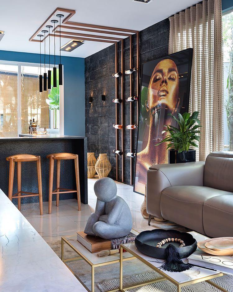 Living integrado com cozinha. Bancada preta com bancos em madeira. Sofá em marrom claro e mesa de centro com obras de arte. Quadro de mulher dourada grande apoiado na parede.