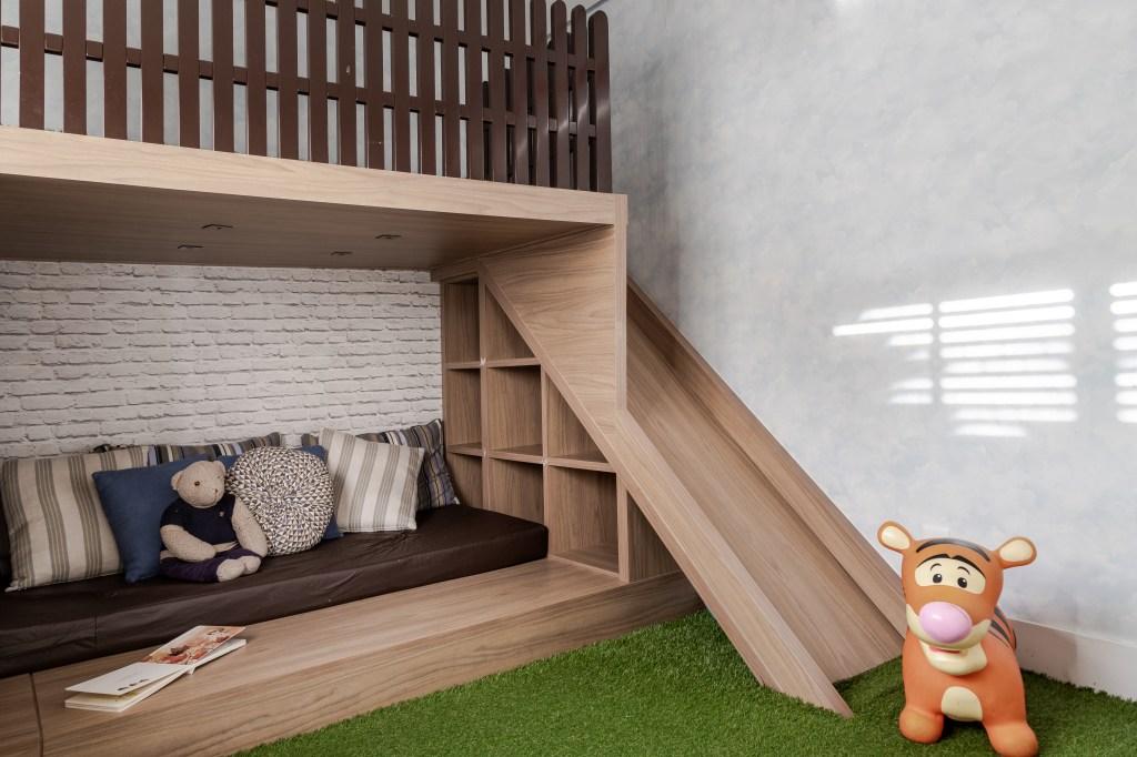 Brinquedoteca com móvel em madeira com escorregador. Sofá com travesseiros listrados. Brinquedo de tigre no chão.